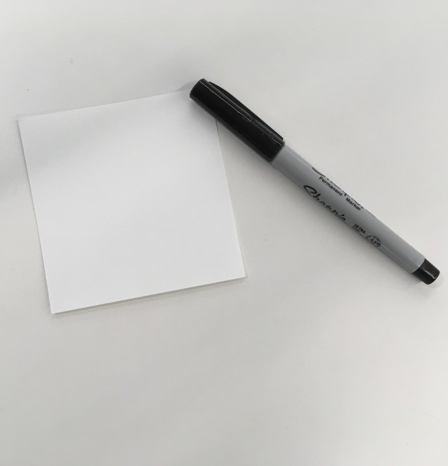 Blank square of paper with marker.