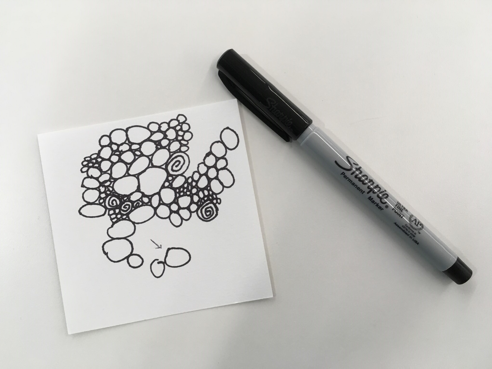 Paper square with more random circles in black ink.