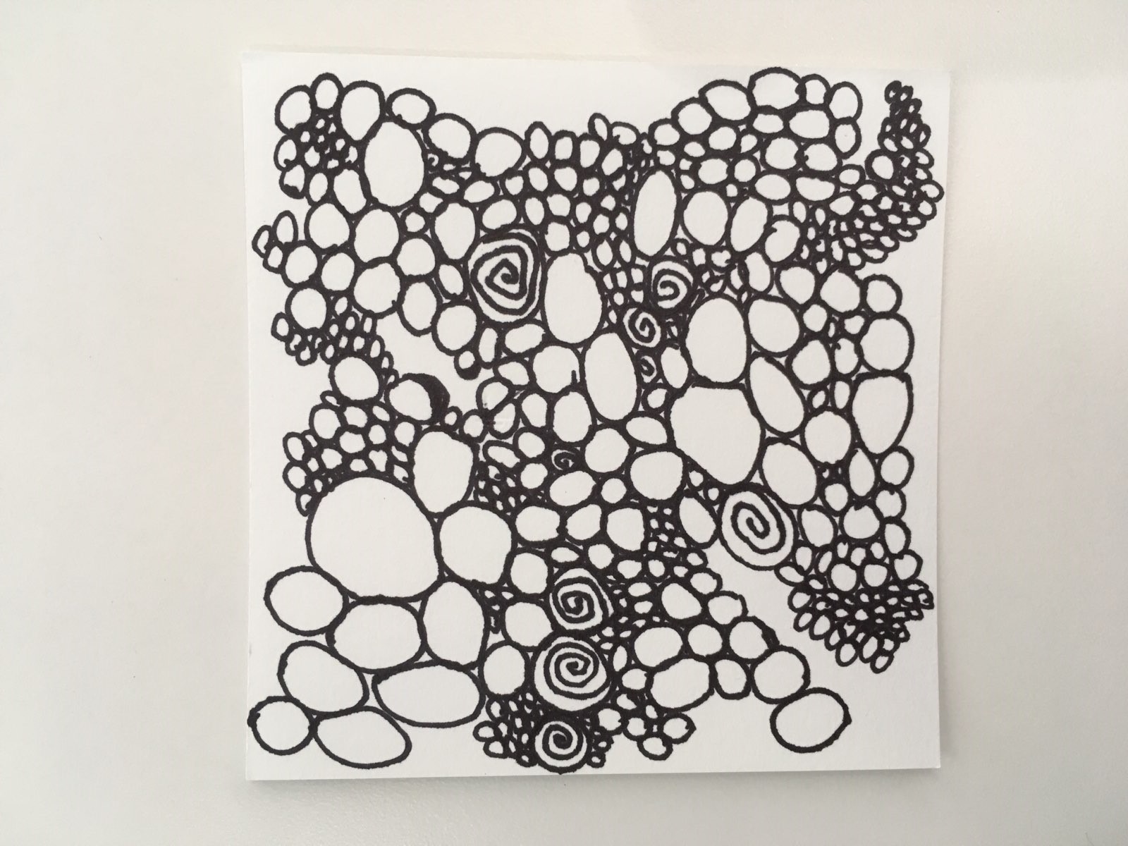 Paper square filled with randomly shaped and placed circles drawn with blank ink lines.