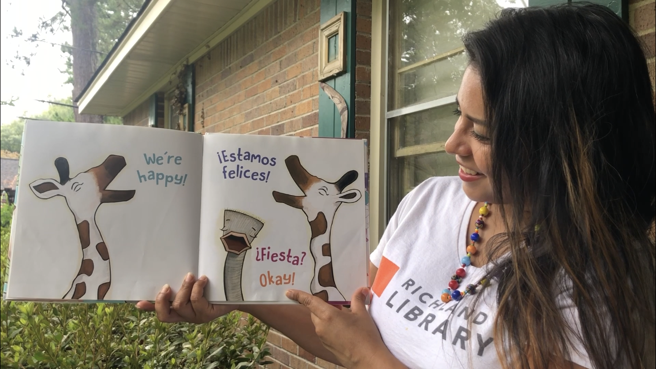 Richland Library staff member reads a bilingual book