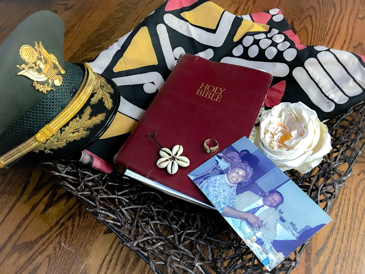 Military hat, brown Bible, photograph of an older Black woman and older Black man, large white flower, and gold engagement ring