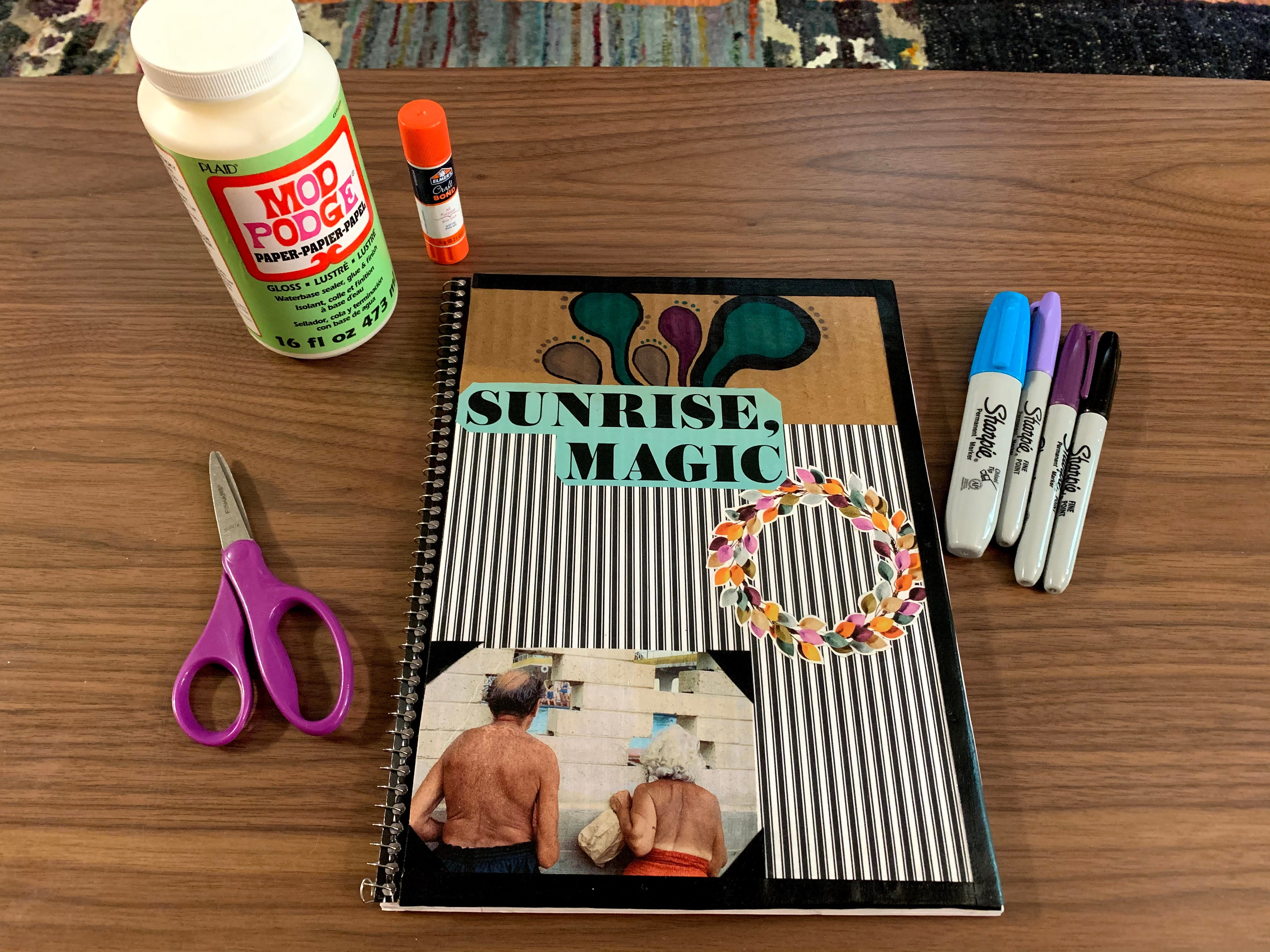 decorated notebook with scissors, glue, and markers nearby