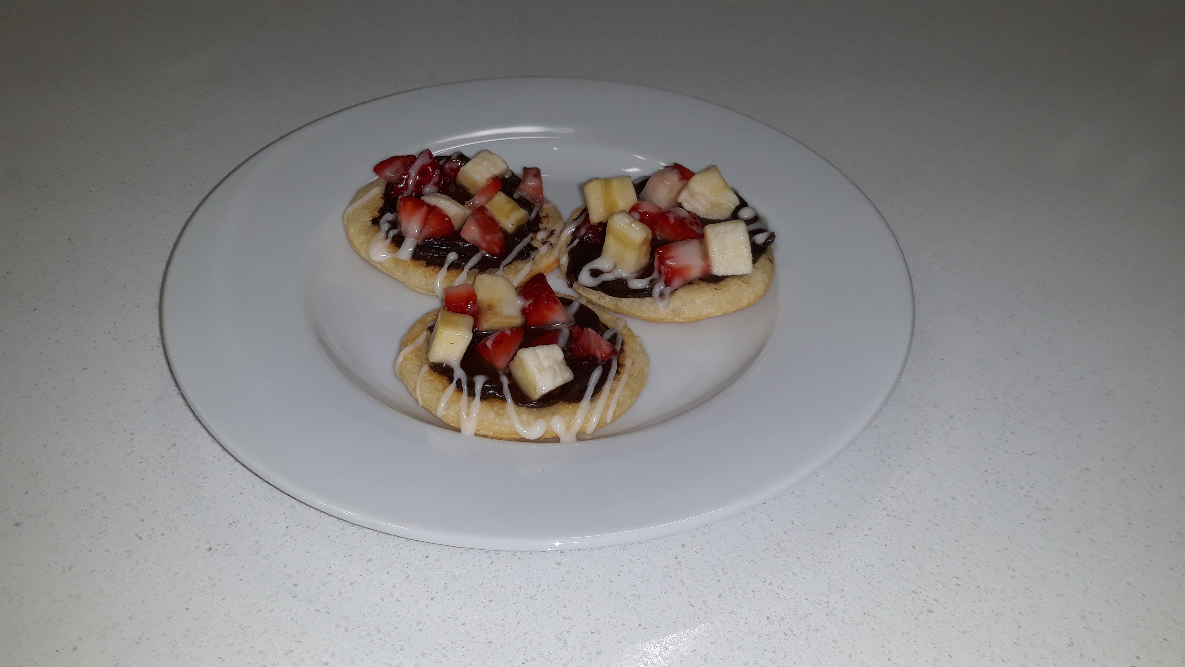 Three fruit and chocolate topped mini pizzas on a white plate.