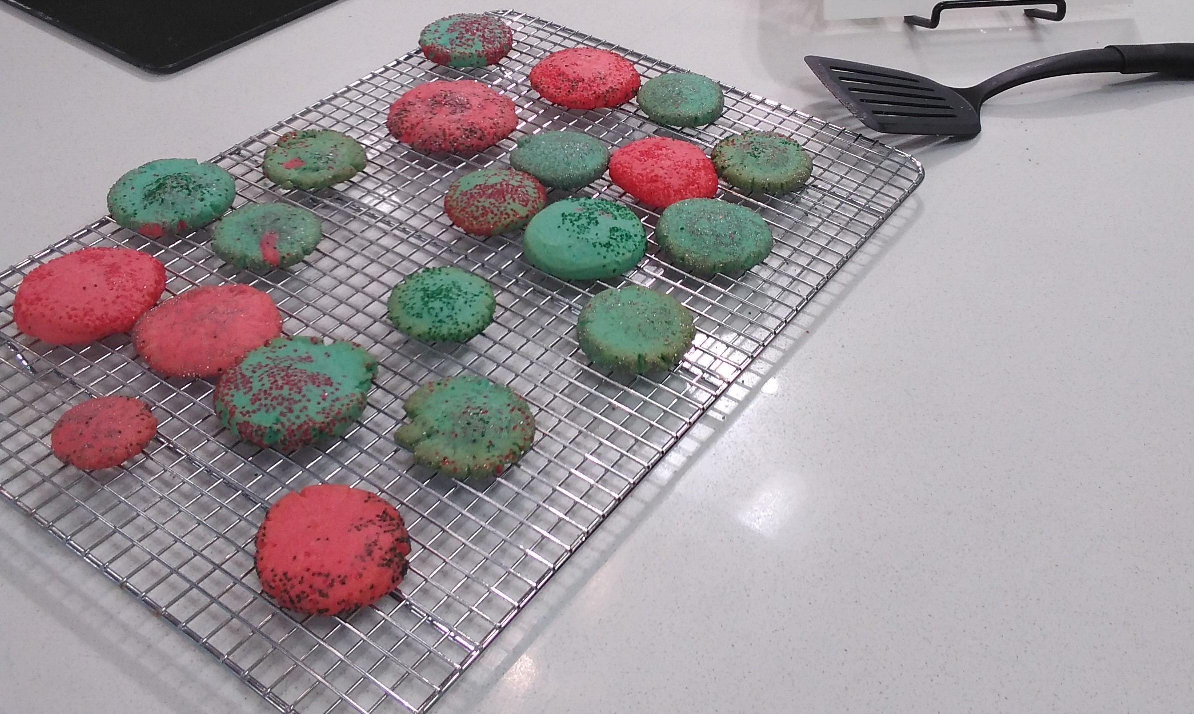 Red and green cookies on a cooling rack.