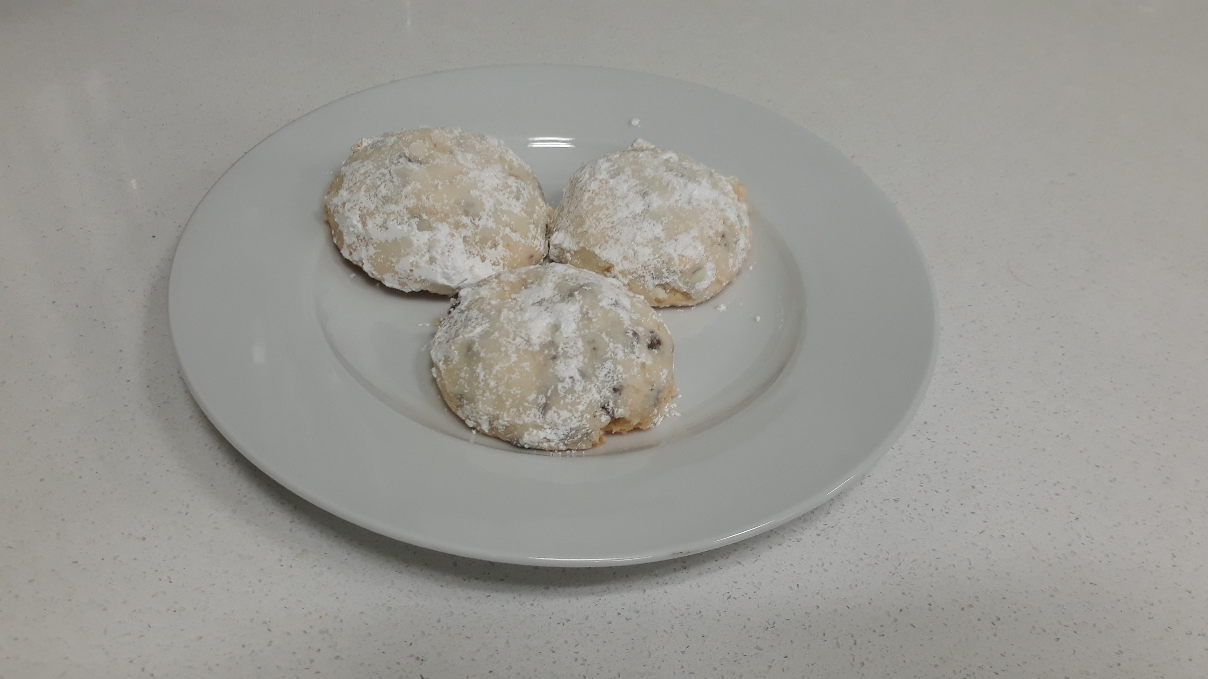 Three snowball cookies on a white plate