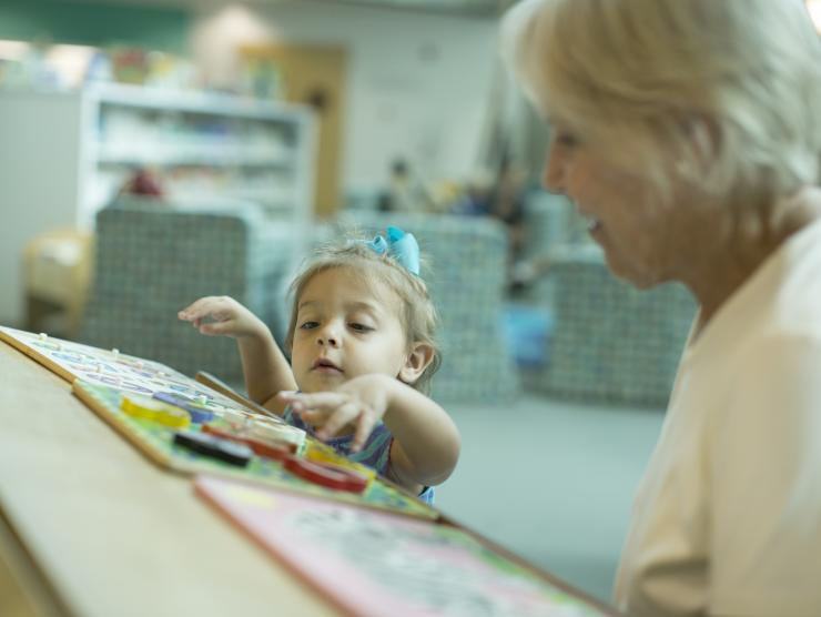 Grandmother and granddaughter play with puzzles in the library