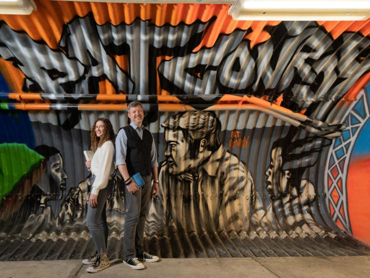 Jonathan Haupt and Holland Perryman of the Pat Conroy Literary center stand back to back in front of a wall of graffiti art celebrating the writer Pat Conroy