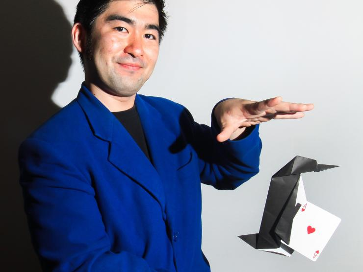 Magic Story Artist Yasu Ishida performing origami and playing card magic trick