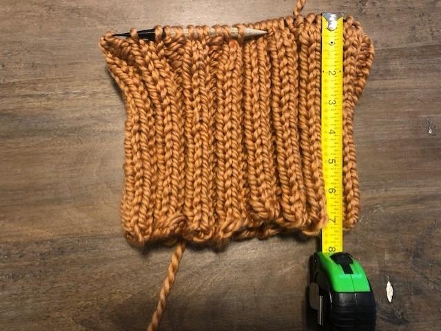 An unfinished knit piece with a 2 by 2 rib and a tape measure showing that it is seven inches long