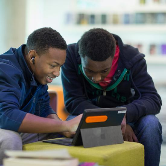 Teen boys looking at a tablet.