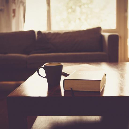 A mug and book on a coffee table with brown couch in background