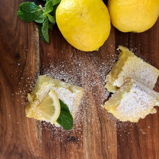 An image of lemons and lemon bar slices on a wooden cutting board
