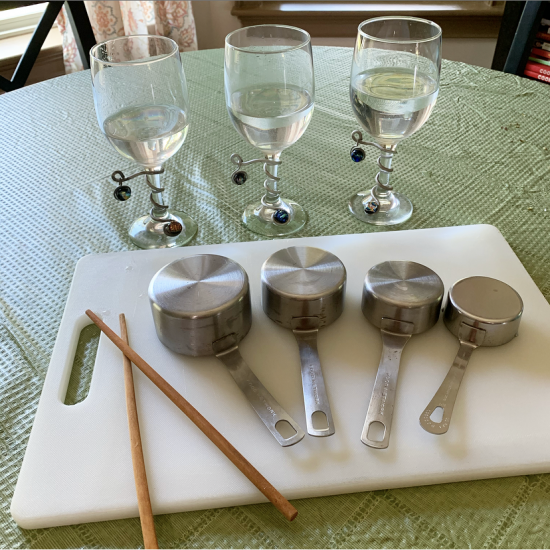 set of metal measuring cups and chopsticks on white cutting board, with three stemmed water glasses in background