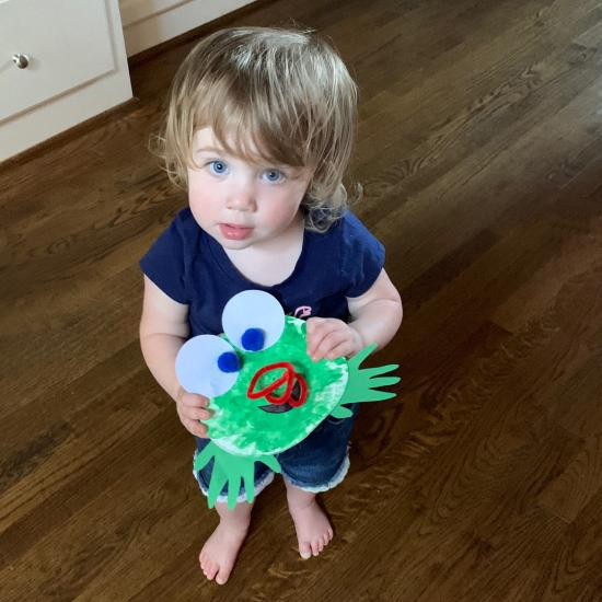 Child with completed frog craft