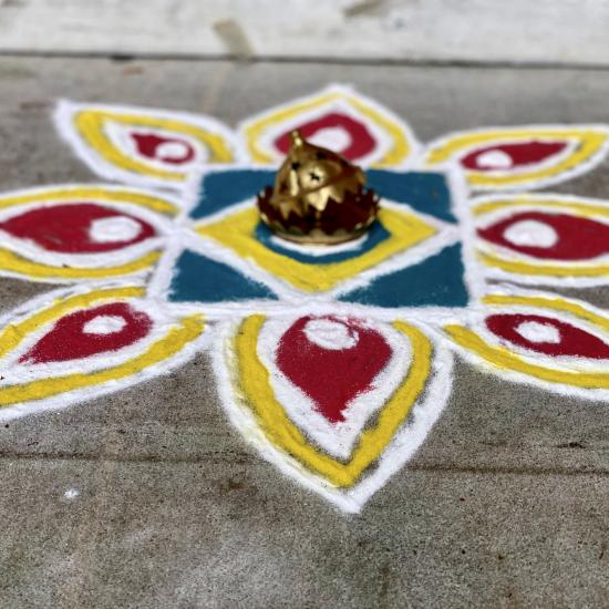 colorful dyed flour arranged in a flower shape on sidewalk, an example of the Indian folk art of Rangoli