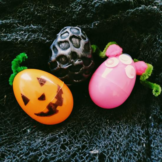 Three plastic eggs decorated to look like a jack-o-lantern, monster and dragon egg