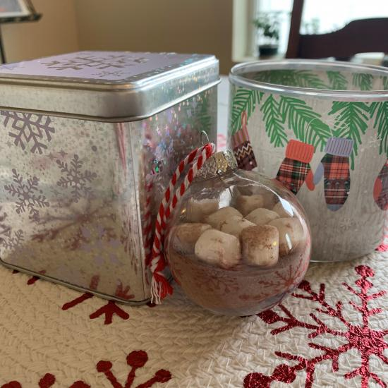 A clear ornament filled with hot cocoa mix and marshmallows, posed against two decorative holiday tins.
