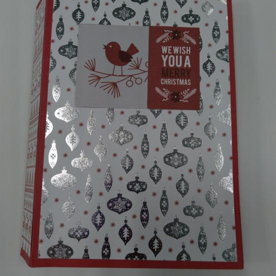 "small handmade book with silver ornaments on the cover. red bird on a branch in the center of the book cover and text: ""We wish you a merry Christmas"""