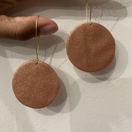 Bronze circular clay earrings with hanging thin wires hanging on two brown skinned fingers, against a white background.