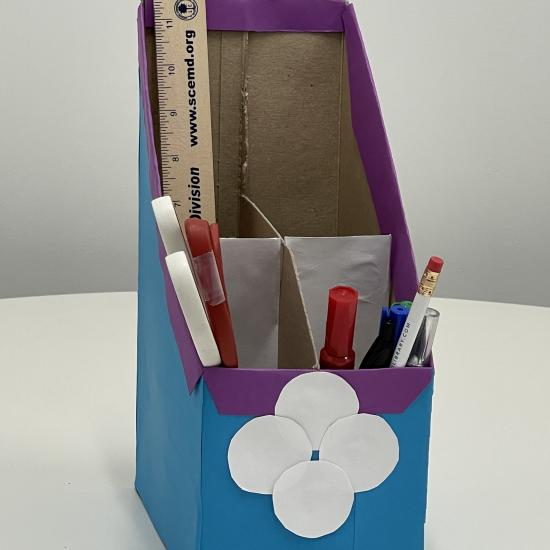 blue, purple, and white desk organizer made out of cardboard;  tan ruler, white and red scissors, red and green markers, white pencil sit are in organizer